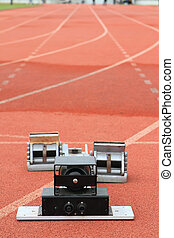 Athletics Starting Blocks on a red running track in a...