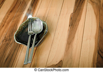 Empty dish, knife and fork on wood table