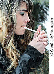 Teen girl lighting cigarette - Young teen girl lighting a...