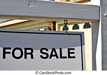 For Sale Sign with Home in Background