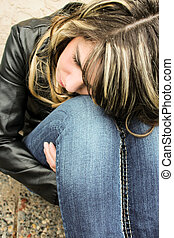 Sad teen with head on knees - Sad teen sitting next to a...