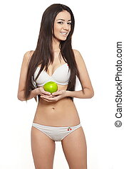 Portrait of beautiful smiling brunette woman in white lingerie with green apple diet isolated on white