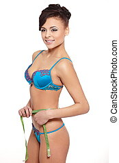 Portrait of beautiful smiling brunette woman in blue lingerie measuring  shape isolated on white