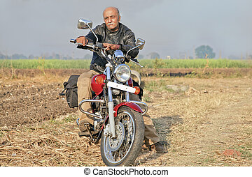 Rural Landcape with senior on a motorcycle - Gujarat India,...