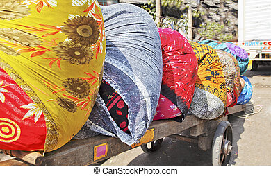 Dhobhi ghat colors wheelcart - colorful bales of laundry on...