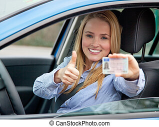 Driving license - Attractive young woman shows her driving...