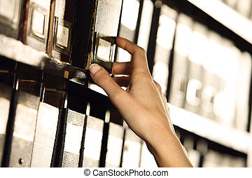 Searching in archives. Student hands searching from a...