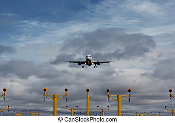 Passenger plane on final approach, with landing lights in...