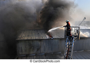 Fire fighter on a ladder truck in heavy smoke