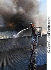 Fire fighter on a ladder truck in heavy smoke