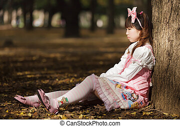 sad japanese lolita leaning against tree in park