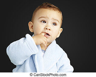 portrait of adorable infant with the finger in his mouth wearing