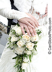 Bridal bouquet of flowers with hands of newlyweds