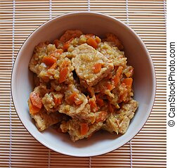 Stew tempeh with carrots, leeks and soy sauce in a bowl