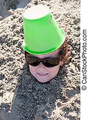 Child buried in the sand - Small child buried in the sand of...