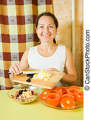 Woman adds grated eggs and sliced olives in mince. See in...
