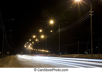 Night street with traces from light of headlights shined...