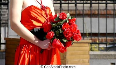 Bride wearing a red wedding dress,carrying a bouquet of rose...