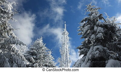 Cellular tower in snow on a blue sky background with clouds passing by