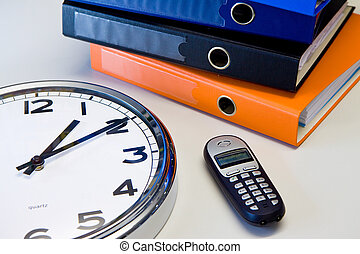 Office stuff - Clock, phone and color binders on the office...