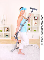 Vacuuming - A picture of a young wife hoovering her...