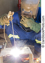 A welder with personal protective equipment welding the...