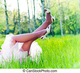 Sexy female legs in perfect green grass