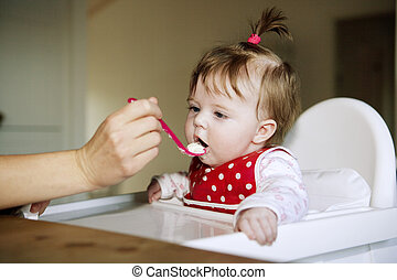 Baby Girl eating - Young Baby Girl eating in the kitchen