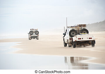 Ute trucks beach driving on tropical fraser island,...