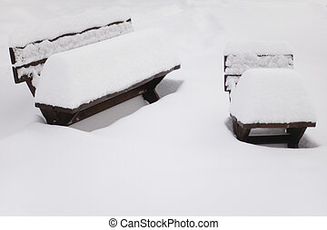 White emptiness - Two garden benches covered with thick...