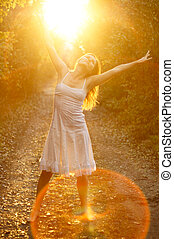 Blissful sunshine - Beautiful young girl dancing in the...