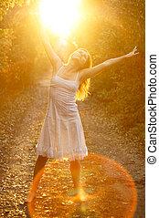Blissful sunshine - Beautiful young girl dancing in the...
