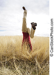Headstand - Young girl doing headstand in a filed of long...