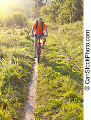 Cyclist on the Riding Bicycle Walk in Summer Nature