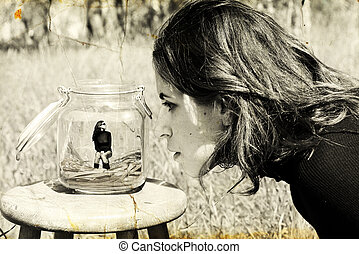 girl looks at herself in the glass jar. Photo in old image...