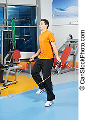positive man at legs exercises with skipping rope