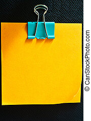 Yellow memo stick with paperclip on black leather