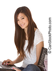 Asian student in jeans with laptop