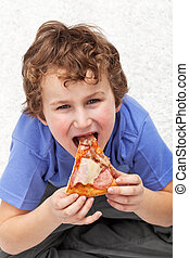 Hungry kid eating pizza