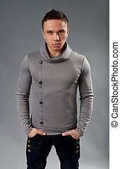 Sexy fit and neat young man in studio. Wearing grey...