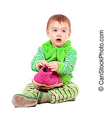 child holding shoes over white