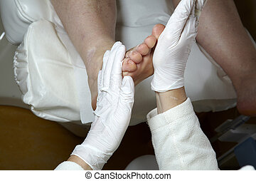 A Pedicurist gives a woman a leg and foot reflexology