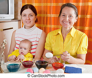 Family coloring eggs for Easter holiday