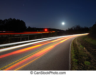 traffic on the road at night - light streaks from traffic on...