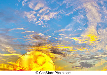 Beautiful multicolored sunrise with golden football ball -...