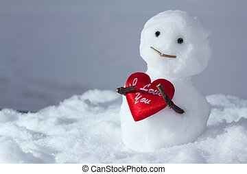 Funny snowman holds a heart