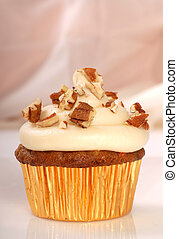 Delicious carrot cake cupcake with cream cheese frosting and chopped pecan nuts