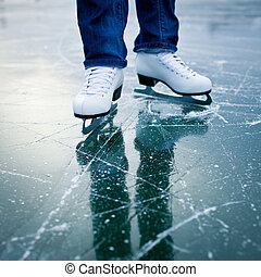 Young woman ice skating outdoors on a pond on a freezing...