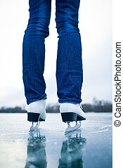 Young woman ice skating outdoors on a pond on a freezing winter day - detail of the legs