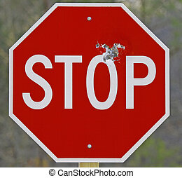 A closeup of a stop sign full of bullet holes along the side...